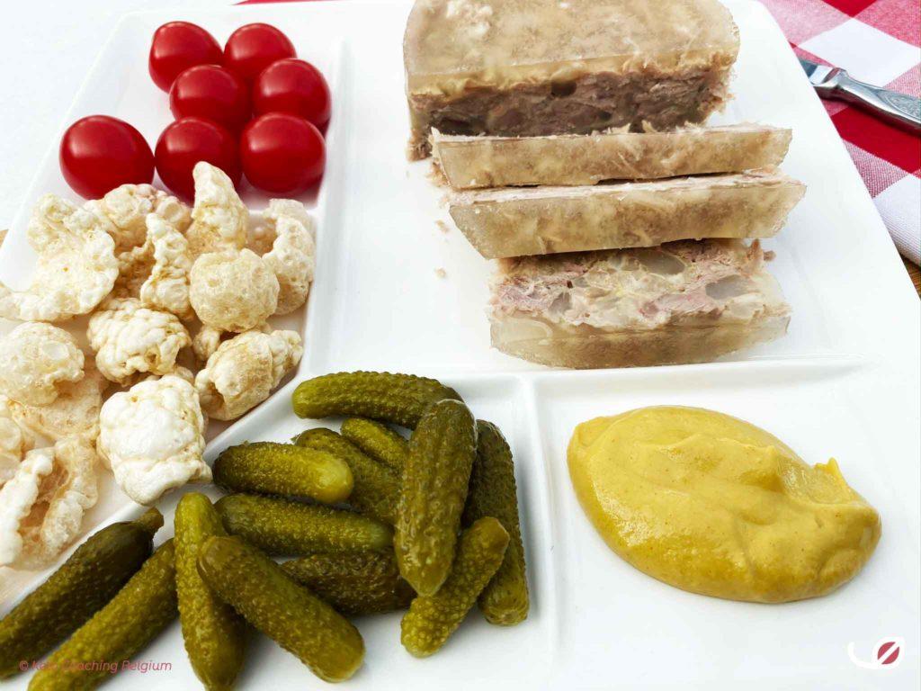 terrine van varkenspoot met augurken mosterd knabbelspek kerstomaat aperitief bord